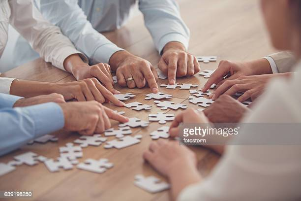 business people putting together jigsaw puzzle - raadsel stockfoto's en -beelden