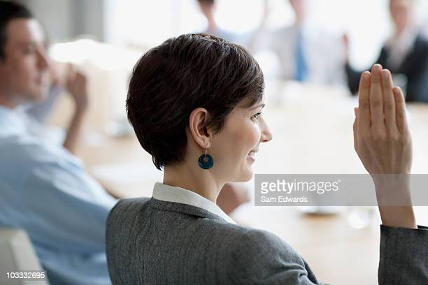 Business people raising hands in meeting in conference room