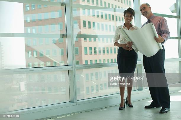 Business people reading blueprints in office