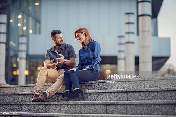 Geschäftsleute entspannen auf Treppe und sprechen über Handy.