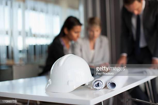 Las personas de negocios revisar blueprints en la sala de conferencias
