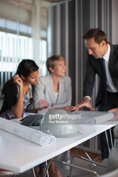 business people reviewing blueprints in conference room - menselijke ledematen stockfoto's en -beelden
