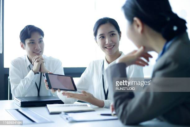 business people reviewing data with digital tablet in meeting - business ストックフォトと画像