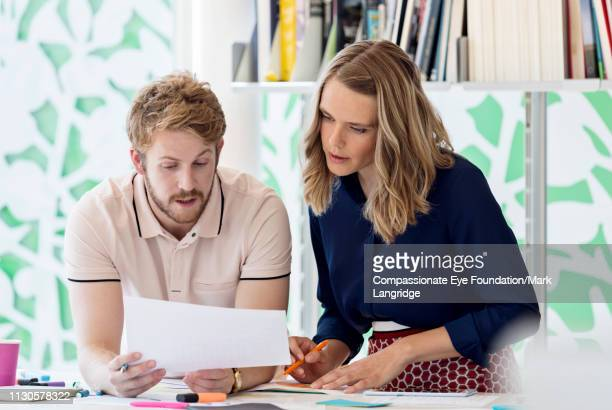 """business people reviewing paperwork in meeting in modern office - """"compassionate eye"""" stock pictures, royalty-free photos & images"""