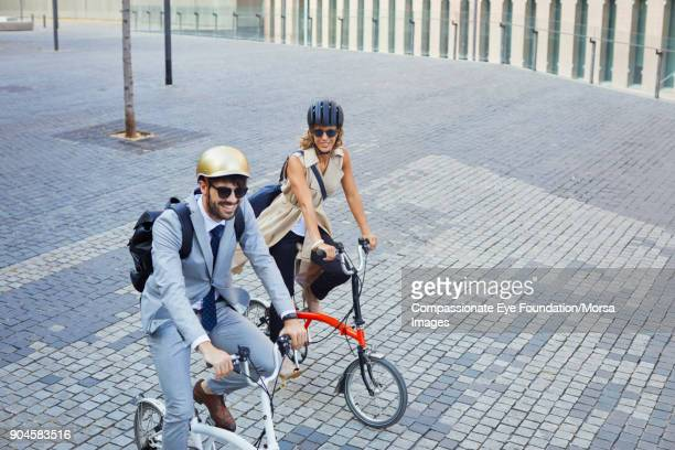 Business people riding bicycles on city street