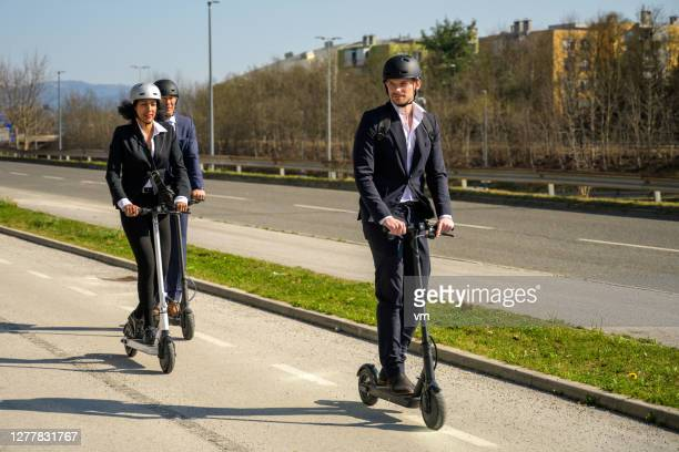 business people riding electric push scooters in the city - electric scooter stock pictures, royalty-free photos & images