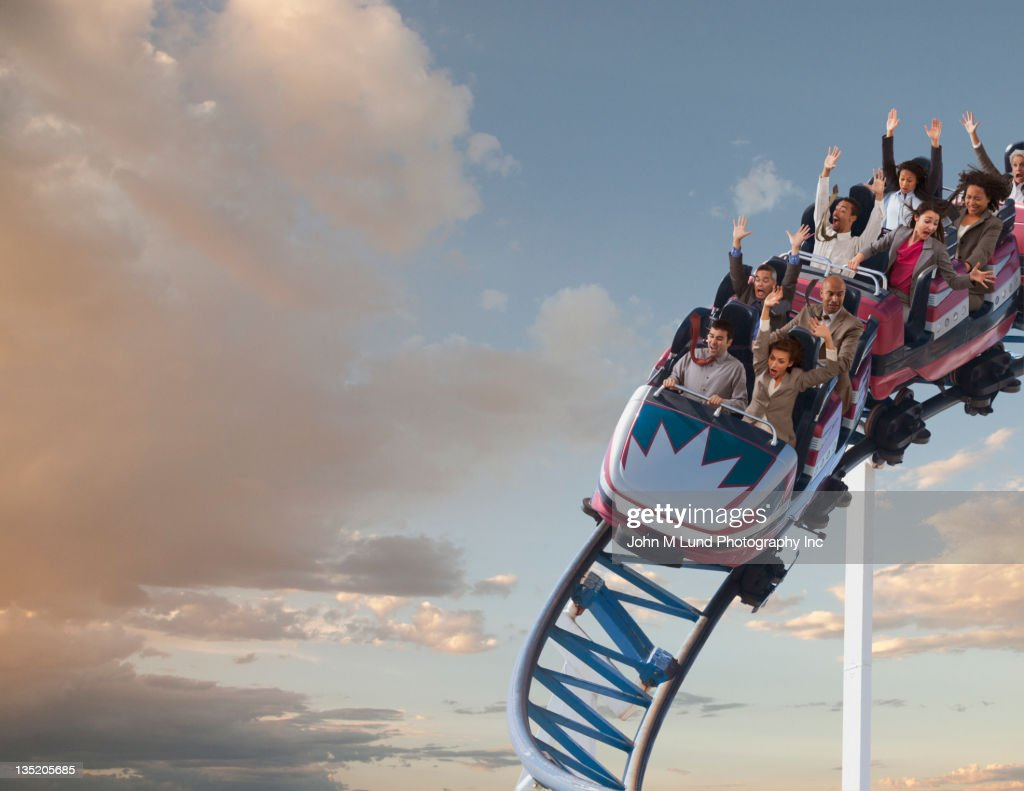 Business people riding roller coaster : Stock Photo