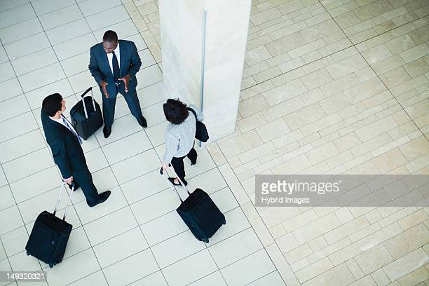 Business people rolling luggage in lobby