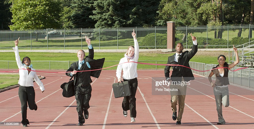 Business people running across track finish line : Stock Photo