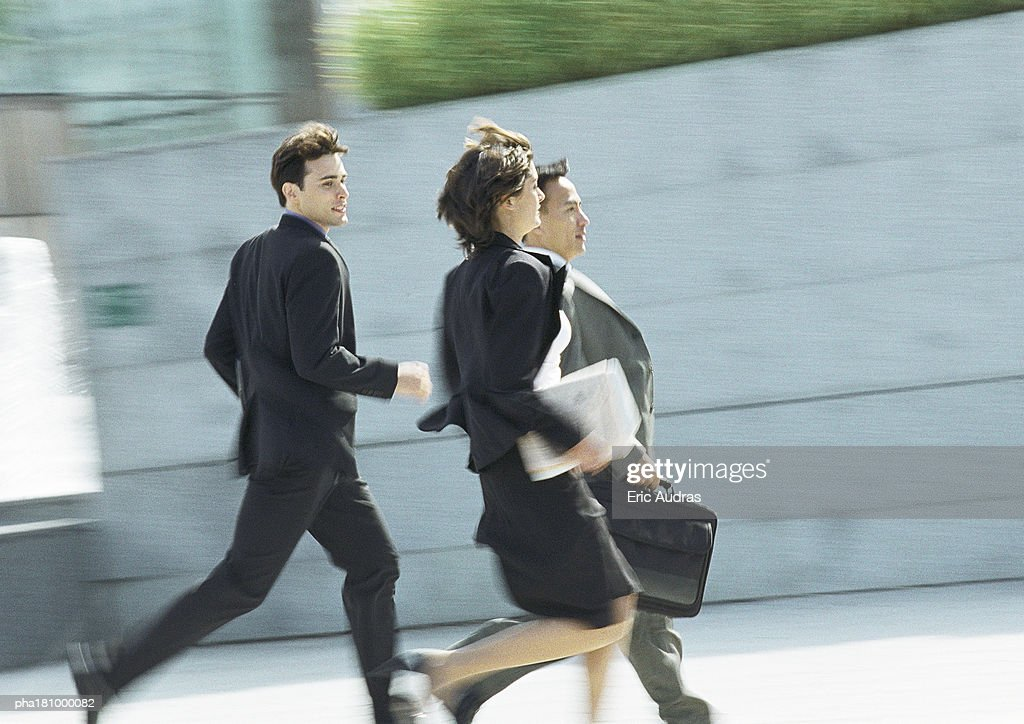 Business people running outdoors, blurred motion : Stockfoto