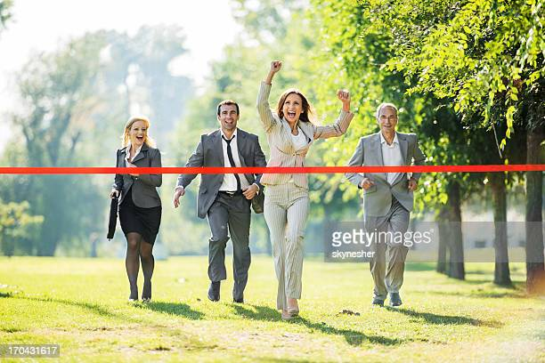Business people running to finish, crossing red line