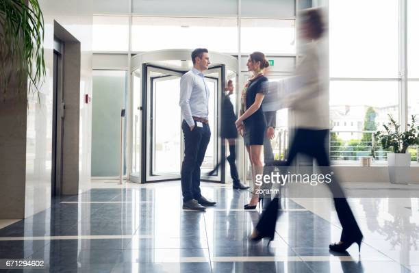Business people rushing past coworkers talking in lobby