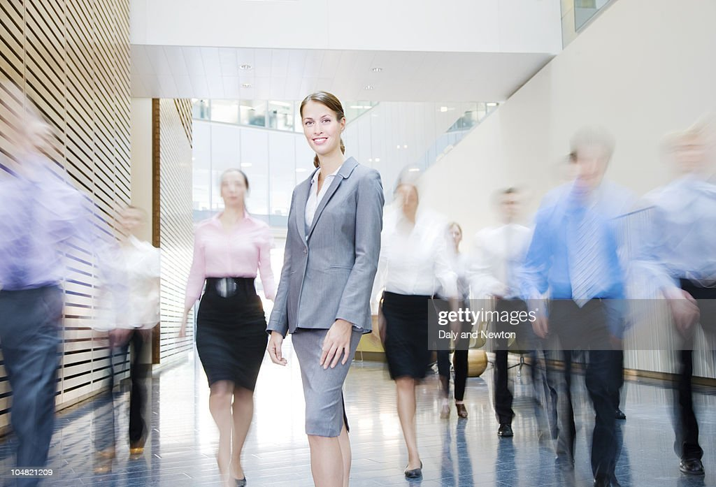 Business people rushing past smiling businesswoman in lobby : Foto de stock