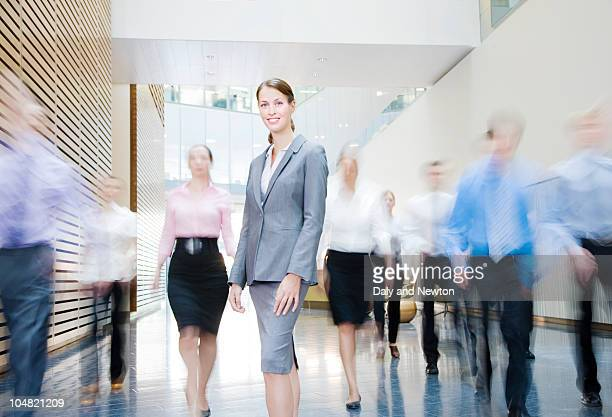 business people rushing past smiling businesswoman in lobby - long exposure stock pictures, royalty-free photos & images