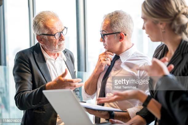business people serious discussing work standing in modern office. - reunião de equipe - fotografias e filmes do acervo
