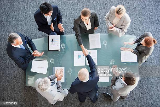 ビジネスの人々の手を振るコンファレンスルームのテーブル