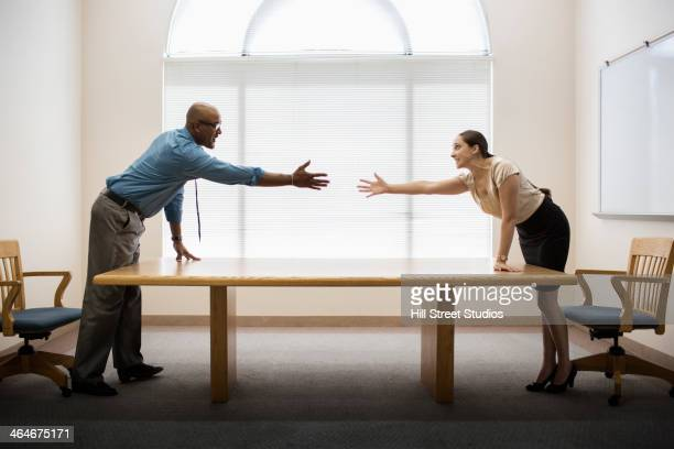 business people shaking hands across table - 手を伸ばす 男性 ストックフォトと画像