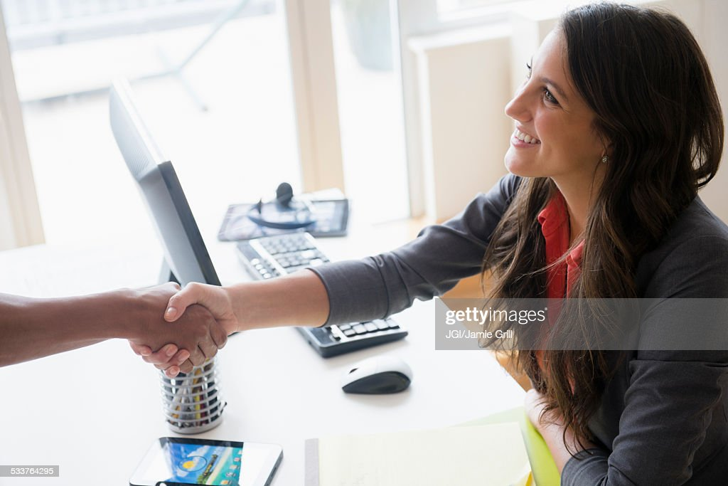 Business people shaking hands at desk in office : Foto stock