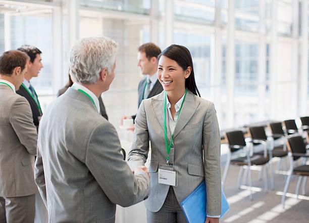 Business people shaking hands at seminar