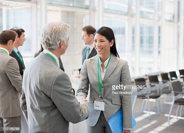business people shaking hands at seminar - bijwonen stockfoto's en -beelden