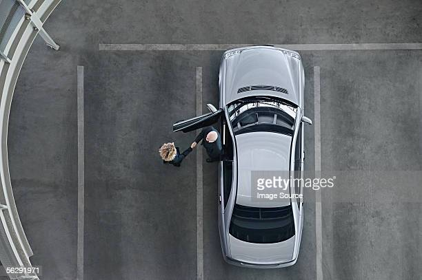 Business people shaking hands by a car
