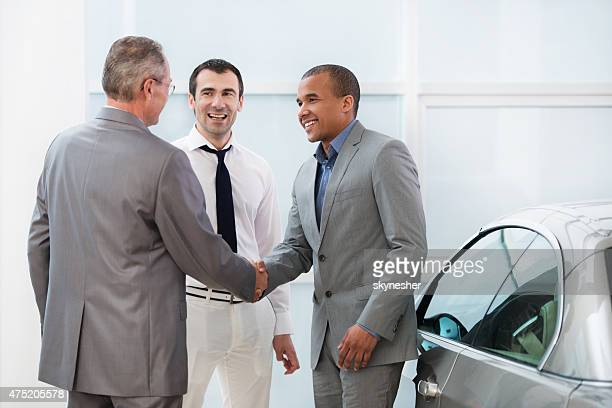 Business people shaking hands in a car showroom.