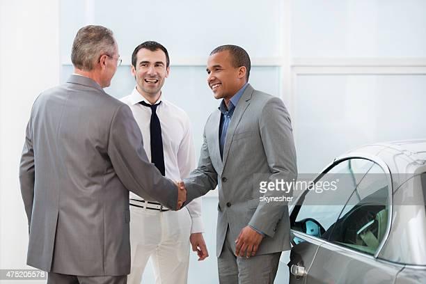 Gens d'affaires se serrant la main dans le showroom automobile.