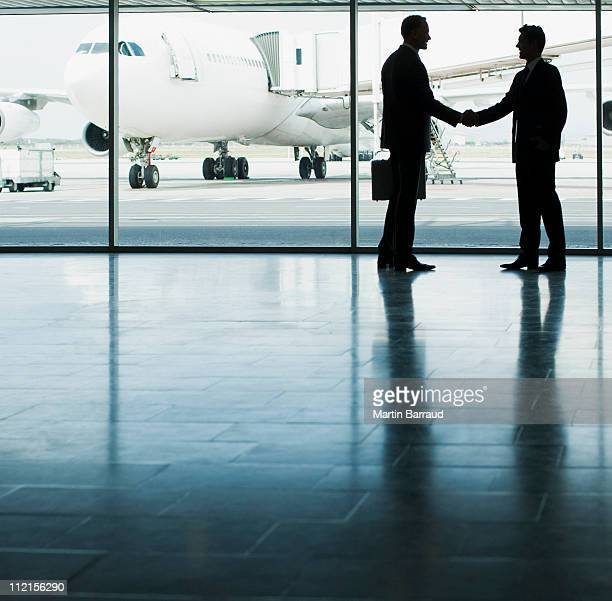 business people shaking hands in airport - luftfarkost bildbanksfoton och bilder