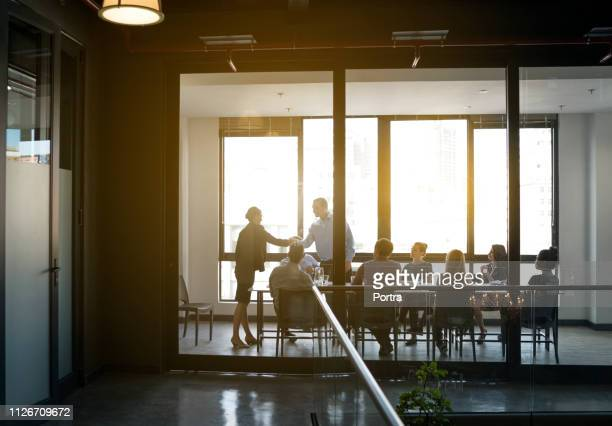 business people shaking hands in board room - board room stock pictures, royalty-free photos & images