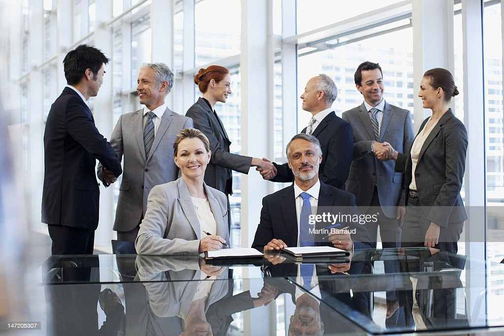Business people shaking hands in conference room : Stock Photo