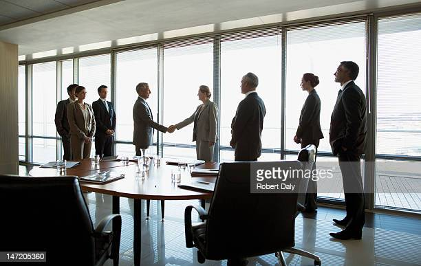 business people shaking hands in conference room - concentratie stockfoto's en -beelden