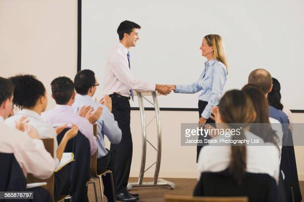 business people shaking hands in front of audience at podium - preisverleihung stock-fotos und bilder