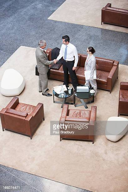 Business people shaking hands in lobby