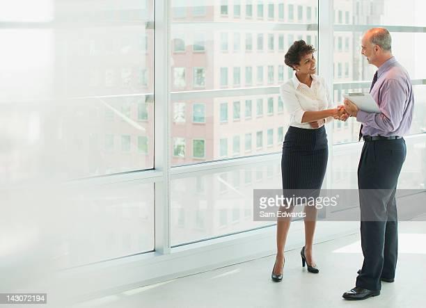 Gens d'affaires se serrant la main dans le bureau