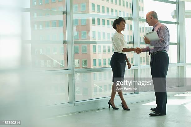 Hombres de negocios estrechándose las manos en la oficina