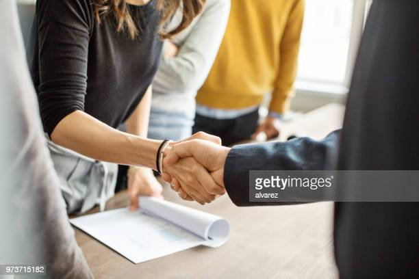 business people shaking hands in office - società foto e immagini stock