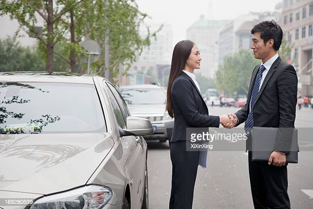 Business People Shaking Hands On Road