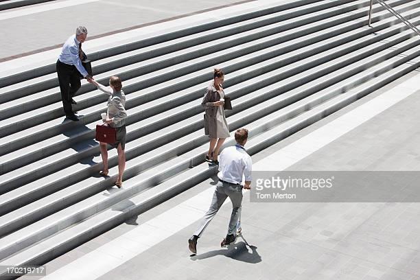 Gens d'affaires se serrant la main sur les marches en plein air