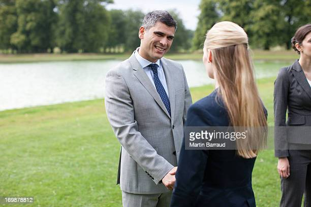Business people shaking hands together outdoors