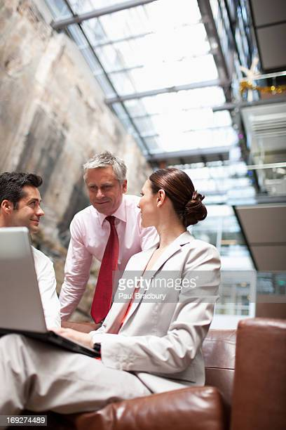 Business people sharing computer on lobby sofa