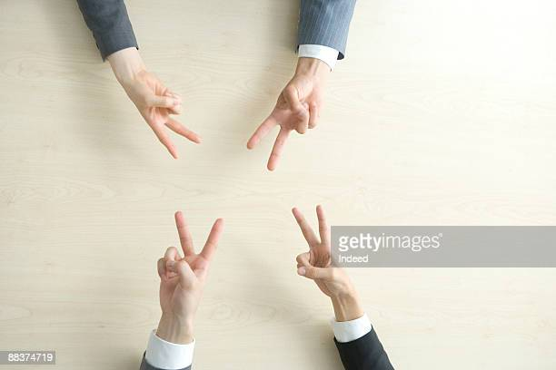 Business people showing peace sign, overhead view