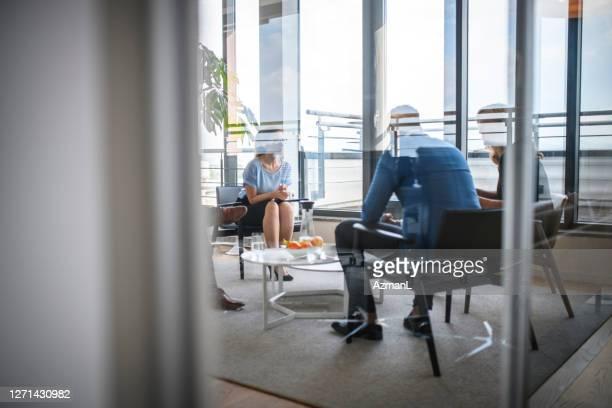 企業ロビーで座って話すビジネスの人々 - 中距離 ストックフォトと画像