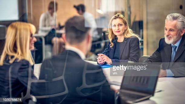 business people sitting at a table and talking - financial analyst stock pictures, royalty-free photos & images