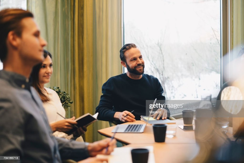 Business people sitting at conference table in brightly lit board room : Stock Photo
