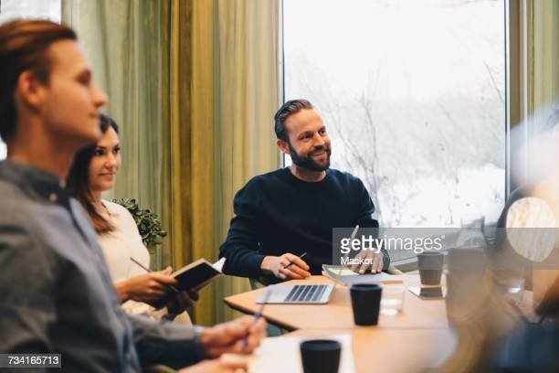 Business people sitting at conference table in brightly lit board room