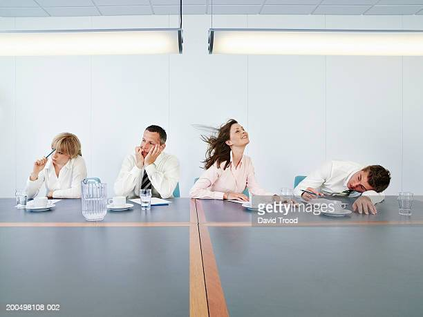 Business people sitting at conference table, one woman smiling