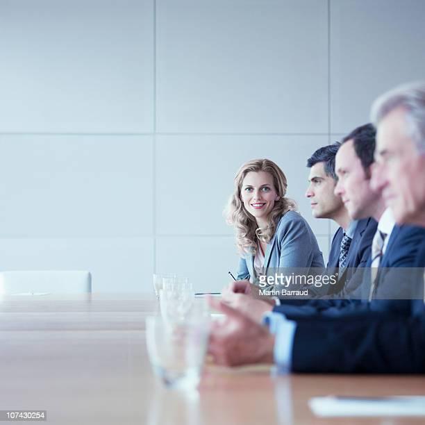 business people sitting at conference table - conferentietafel stockfoto's en -beelden
