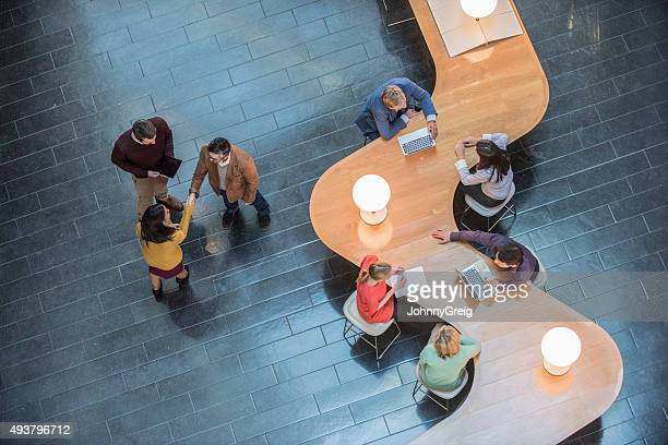 Business people sitting at curved wooden desk, high angle view