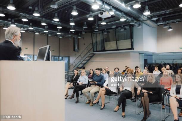 geschäftsleute, die am seminar sitzen - podiumsdiskussion stock-fotos und bilder