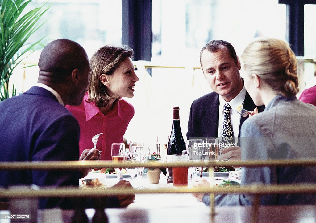Business people sitting at table, eating, close up. : Stockfoto